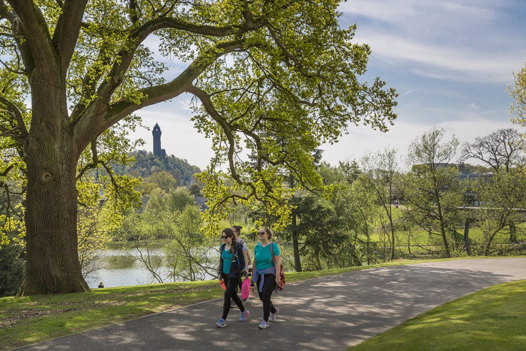 Woman walking around Airthrey Loch at Stirling University, Wallace Monument in background