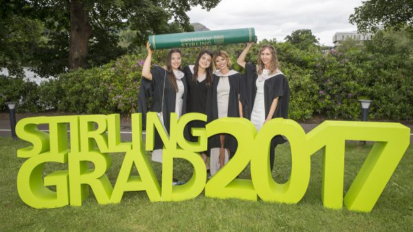 Stirling graduates holding Graduation props next to Airthrey Loch at summer Graduation 2017