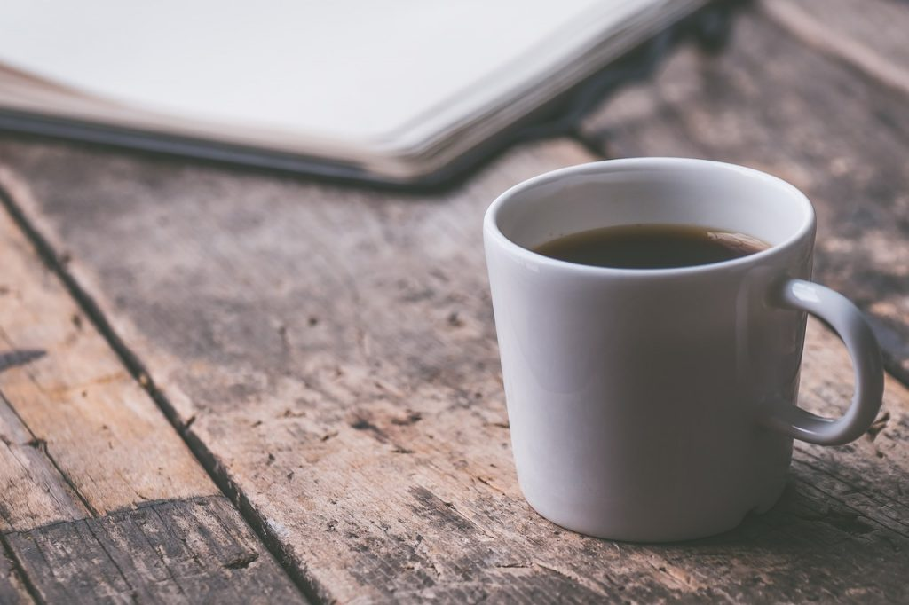 Coffee and a notepad on a desk – all part of a balanced routine – ideal if you're planning a return to study.