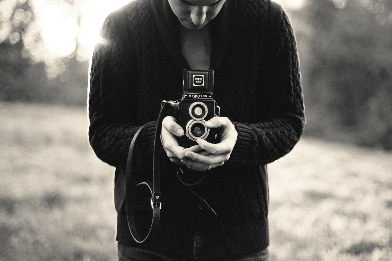 A young person holding an old film camera.