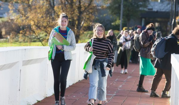 Two girls walking across bridge on University of Stirling campus during an Open Day