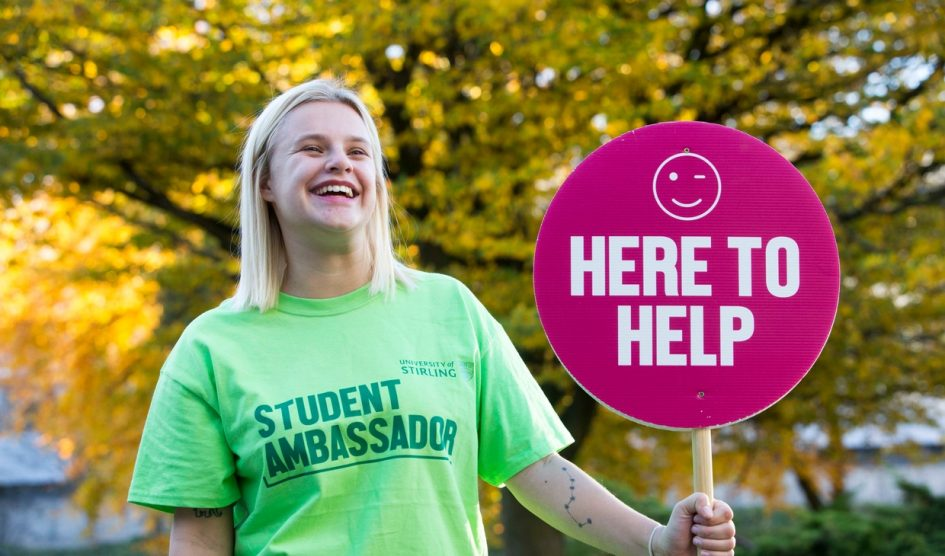 Student ambassador at Open Day with a 'here to help' sign