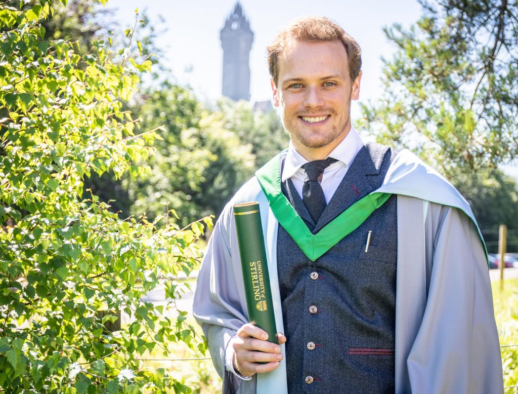 Man smiling in graduation gown with Wallace Monument in the background