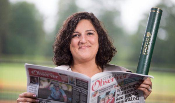 Girl at graduation holding newspaper