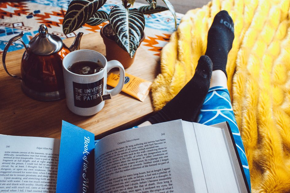 Person relaxing at home, drinking tea and reading a book looking after their mental health