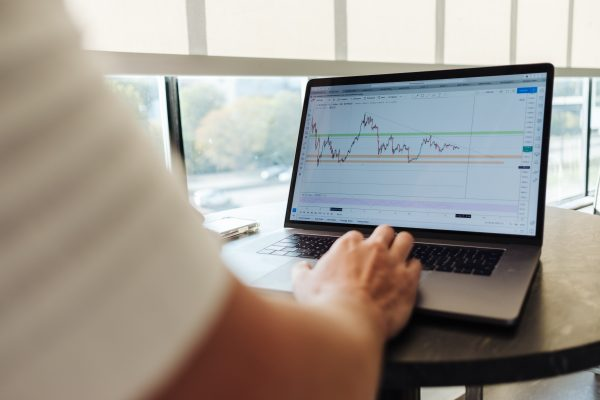 Man looking at a financial graph on a laptop