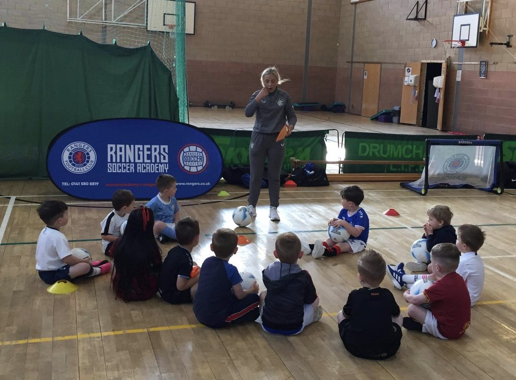 Children sitting in a circle in sports hall