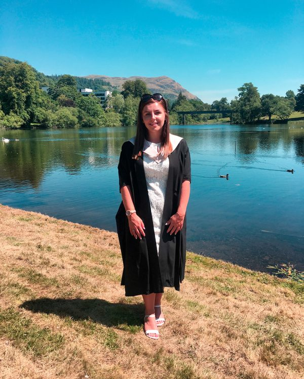 Lucy Walkup in graduation gown infront of a loch