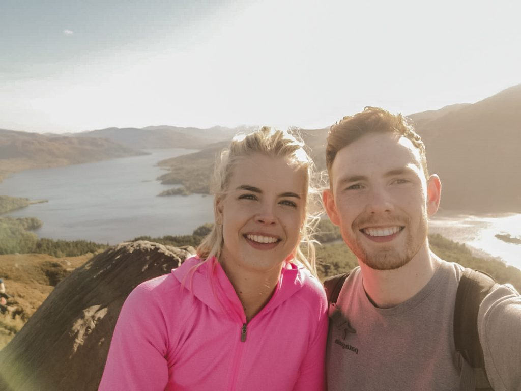 Man and woman smiling at the top of a mountain with a loch behind them.