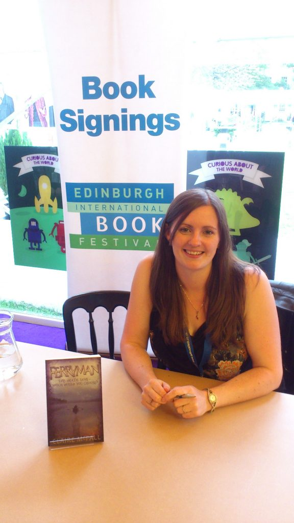 Woman smiling at book signing, with her book beside her.
