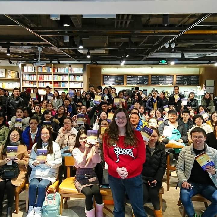 Author standing up with audience behind her at a book event in China.