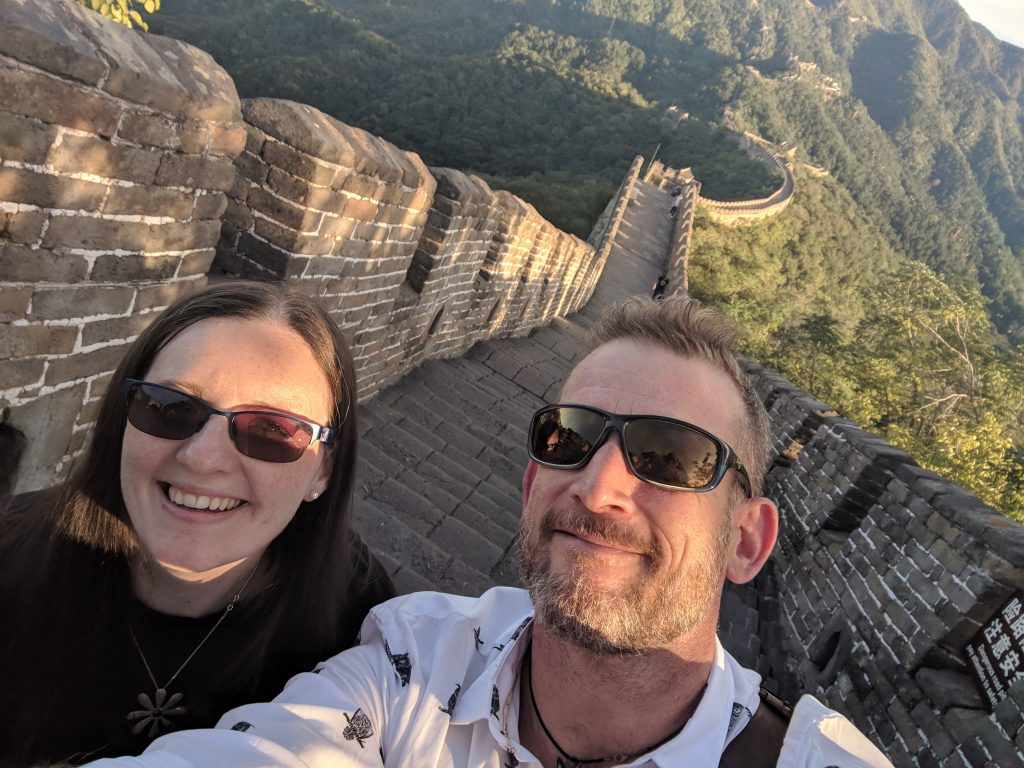 Man and woman smiling whilst on the Great Wall of China.