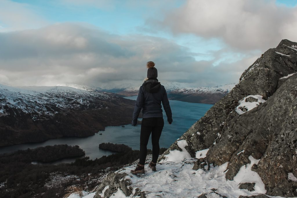 Woman at the top of mountain overlooking a loch.