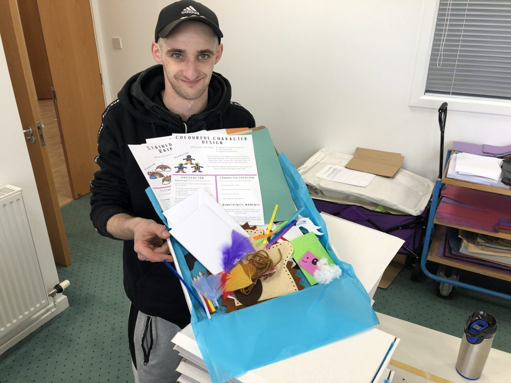 A man holding a Craft Kids box with arts and crafts materials inside.